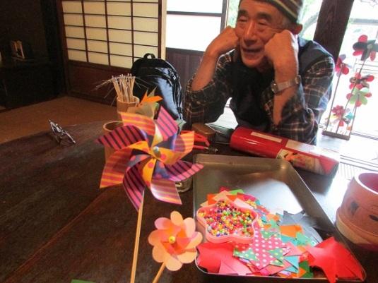 Di rumah-rumah tradisional tua itu, ada staf yang siap membantu menunjukkan cara menggunakan perapian, ataupun mengajarkan cara membuat mainan tradisional Jepang, seperti kakek ini.